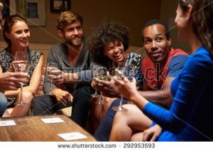 stock-photo-group-of-friends-sitting-around-a-table-at-house-party-292953593