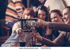 stock-photo-young-cheerful-female-friends-taking-selfie-in-pub-using-digital-tablet-201976576